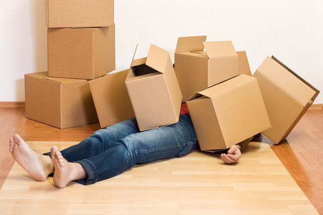 Man lying under pile of boxes